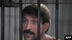 Viktor Bout talks to reporters as he stands in a temporary cell ahead of a hearing at the Criminal Court in Bangkok on August 20.