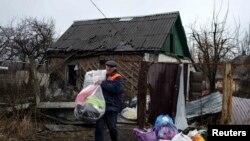 Donetskdə evi dağıdılmış kişi əşyalarını daşıyır
