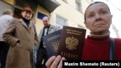 Жена показва двата си паспорта - украински и руски. Снимката е архивна.