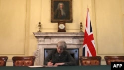 Ұлыбритания премьер-министрі Тереза Мэй елдің ЕО-даны шығу келіссөзін бастайтыны туралы ресми хатқа қол қойып отыр. Лондон, 28 наурыз 2017 жыл.