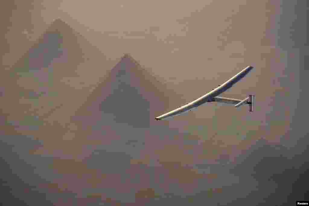 Solar Impulse 2, a solar-powered plane piloted by Swiss pioneer Andre Borschberg, is seen flying over the pyramids of Giza prior to the landing in Cairo on July 13. (Jean Revillard, via Reuters)