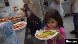 Девочка с едой в лагере для беженцев в Берлине. 9 июня 2016 года.