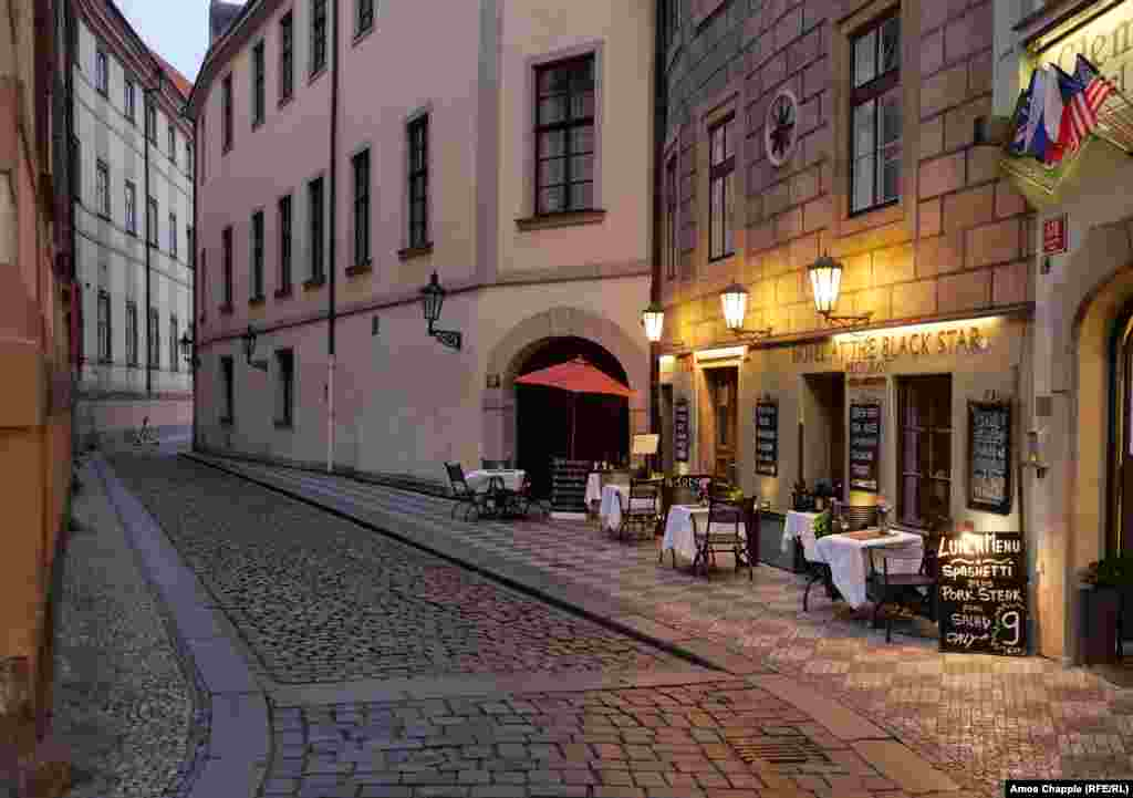 An empty restaurant dining area in Prague's Old Town at dusk.