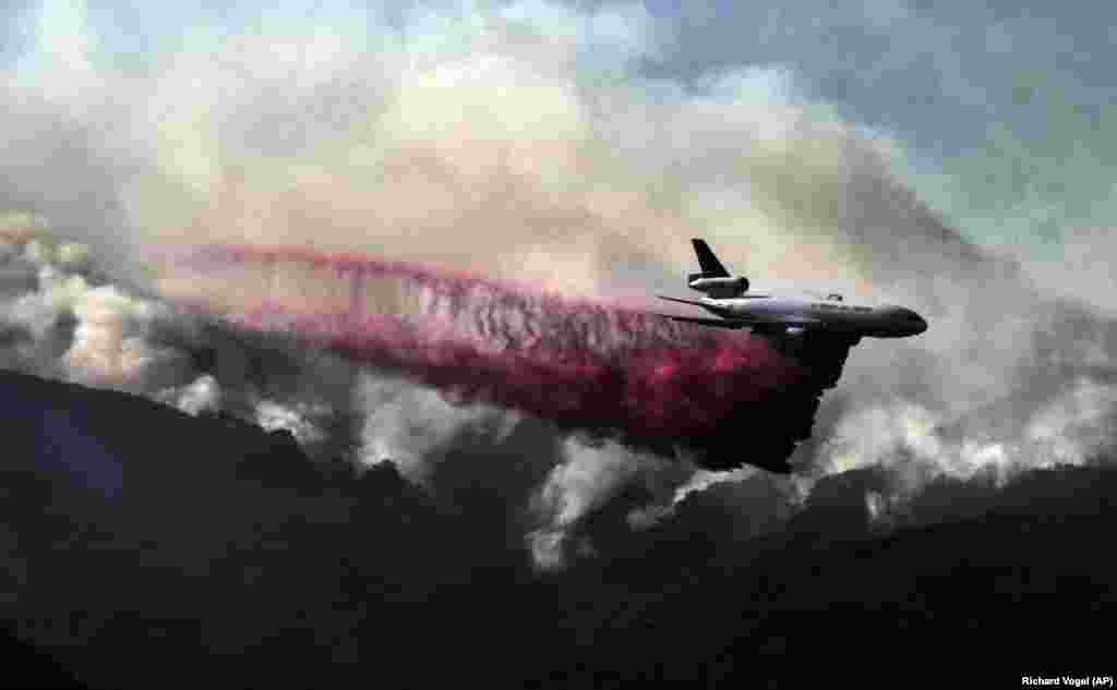 A firefighting DC-10 makes a fire-retardant drop over a wildfire in the mountains near Malibu Canyon Road in Malibu, California, on November 11. (AP/Richard Vogel)