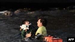 Ребенка спасают вместе с другими мигрантами с тонущего судна в Эгейском море, близ берегов Греции. 30 октября 2015 года.