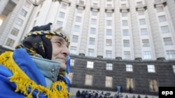 A woman with a national flag around her shoulders attends an opposition rally in front of the Cabinet of Ministers building in downtown Kyiv on November 27.