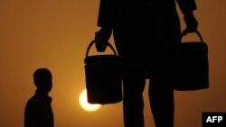 Пакистанец несет ведра с водой в период жары. Иллюстративное фото.
