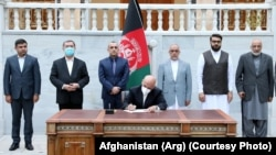 Afghan President Ashraf Ghani signs the decree on the release of the final 400 Taliban prisoners in Kabul on August 10.