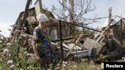 Жінка біля свого зруйнованого будинку в Днецькій області
