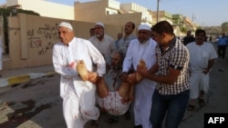 Iraqis carry a wounded man at the scene of a car bomb attack in the northern Iraqi city of Kirkuk on October 15.