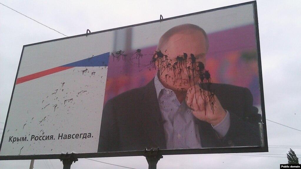Запачканный краской билборд с изображением президента России Владимира Путина. Керчь, сентябрь 2015 года