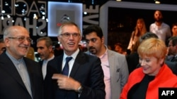 Carlos Tavares (C), chairperson of the managing board of French carmaker PSA Peugeot Citroen, talks flanked by Iranian Industry Minister Mohammad Reza Nematzadeh (L) and Citroen carmaker CEO Linda Jackson during his visit to the PSA Peugeot Citroen stands