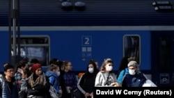Călători purtând măști de protecție