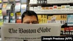 Мужчина с номером американской газеты Boston Globe. Бостон, 15 августа 2018 года.