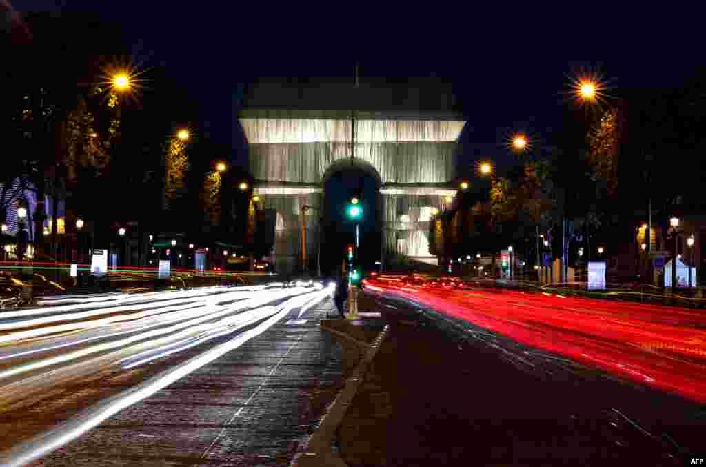 Опакованата Триумфална арка през нощта. Във всичките си проекти Кристо обръща особено внимание на това как светлината взаимодейства с материята.