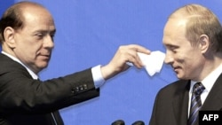 Италия премьер-министрі Сильвио Берлускони (сол жақта) баспасөз мәслихаты кезінде Ресей президенті Владимир Путинге қалжыңдап тұр. Мәскеу, 21 сәуір 2004 жыл.