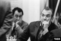 Виктор Корчной 1973 жылғы жарыста. Артқы планда шахмат ойнап отырған Тигран Петросян.