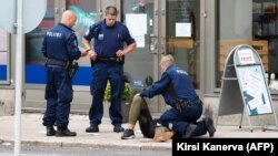 Полицейлер пышақталған адамға көмек көрсетіп жатыр. Финляндия, Турку, 18 тамыз 2017 жыл.