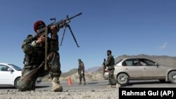 Afghan National Army soldiers stand guard at a checkpoint on the outskirts of Kabul on April 17.