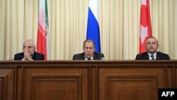 Russian Foreign Minister Sergei Lavrov (center), his Turkish counterpart, Mevlut Cavusoglu (right), and Iranian Foreign Minister Mohammad Javad Zarif speak to the press in Moscow on December 20.