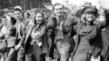 UK -- happy group marches down a London street on VE Day.