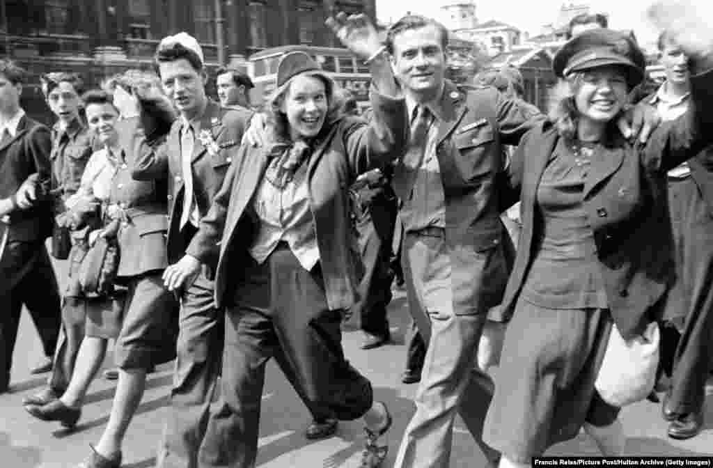 "Young servicepeople march through London. Some lasting relationships began amid the party. Teenager Susan Neilly was celebrating in Belfast when a 16-year-old boy called Bertie ""came up, grabbed me and gave me a big kiss."" The two later married and had a son and daughter. They remained together until Bertie died in 2012."