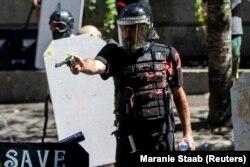 Alan Swinney rendőr fog fegyvert egy tüntetőre, miközben többek közt a Proud Boys és a Patriot Prayer csoportjai összecsapnak a rendőri erőszak és a faji diszkrimináció ellen tüntetőkkel 2020. augusztus 22-én az oregoni Portlandben.