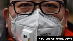 شهروند چینی در شهر شانگهای چین در حالی که بر صورت ماسک زده در ۲۲ ژانویه؛ پژوهشگران و دانشمندان در تلاش هستند تا به رد پای ویروس در مراحل اولیه شیوع آن دست پیدا کنند.