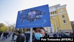 Алматыдағы наразылық жиынында Қытайға қарсы плакат ұстап тұрған адам. 31 қашан, 2020 жыл.