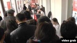Очередь желающих снять свои депозиты на волне слухов о предстоящем банкротстве нескольких коммерческих банков. Алматы, 18 февраля 2014 года.