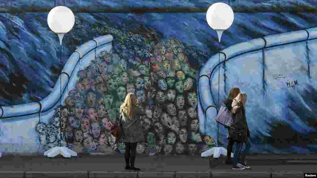 Люди гуляют вдольстендов с воздушными шарами, размещеннымивдоль бывшей Берлинской стены. 7 ноября 2014