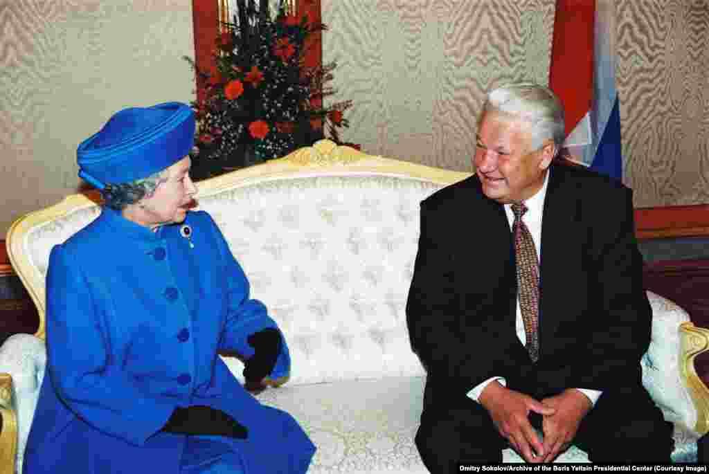Королева Великобритании Елизавета II беседует с тогдашним президентом России во время ее визита в Россию в октябре 1994 года. Эта поездка стала первым визитом британского монарха в Россию с тех пор, как отношения между двумя странами были испорчены большевиками, которые убили в 1918 году царя Николая II и его семью. Русский царь был двоюродным братом дедушки королевы Елизаветы