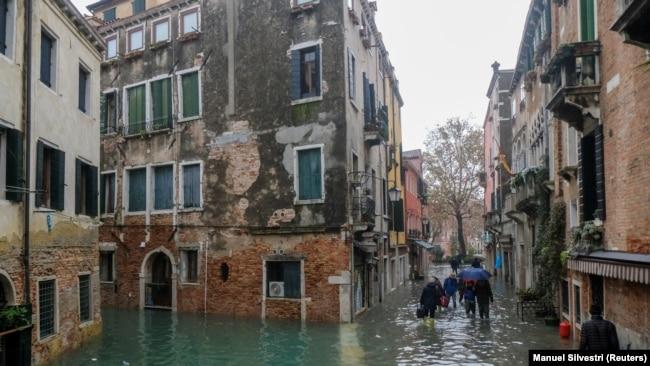 Njerëzit ecin në rrugët e përmbytura nga uji në Venecia.