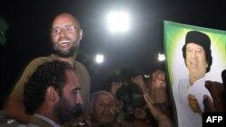 Сейф-аль-Іслам аль-Каддафі біля портрету його батька, фото 2011 року, до скинення режиму Каддафі