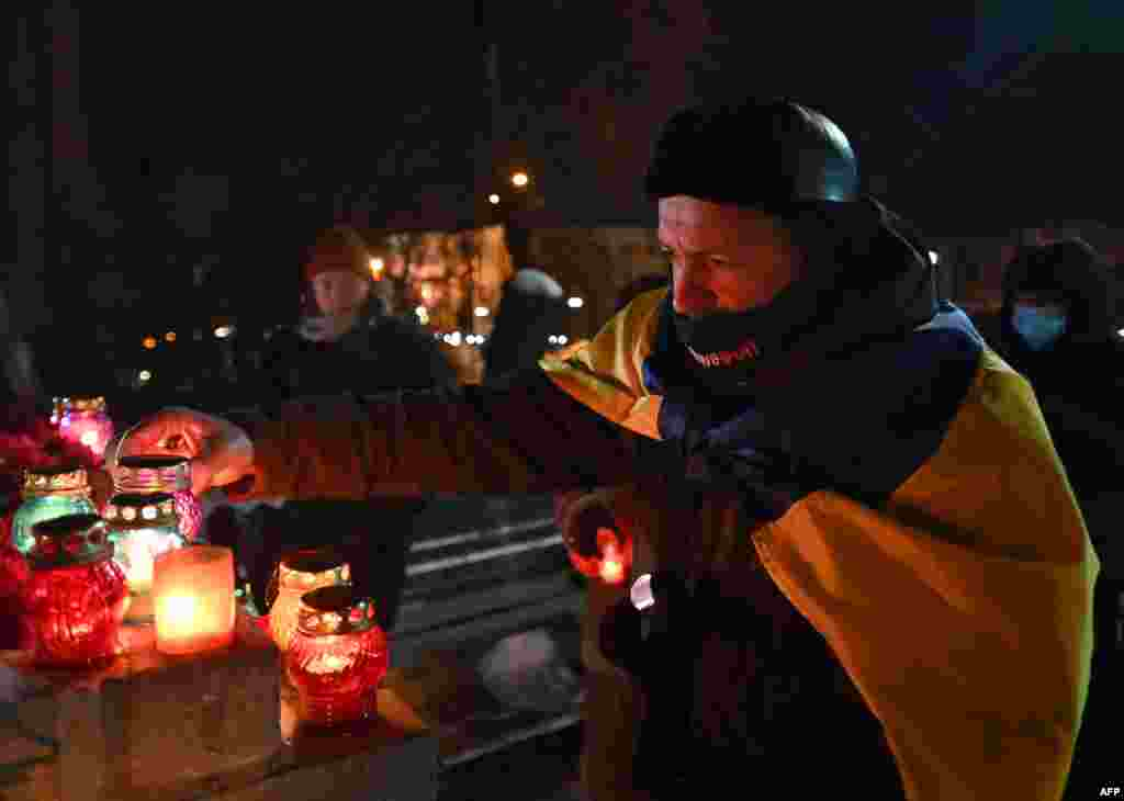 This man lights a candle at the memorial...