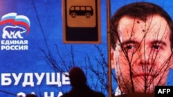 People pass by an election poster of the United Russia ruling party in Moscow.