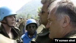General Ratko Mladic (right) confers with Dutch peacekeepers in Srebrenica in July 1995.