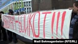 Кезектен тыс президент сайлауына бойкот жариялау туралы жазу ұстап тұрған қоғам белсенділері. Алматы, 25 наурыз 2011 ж.
