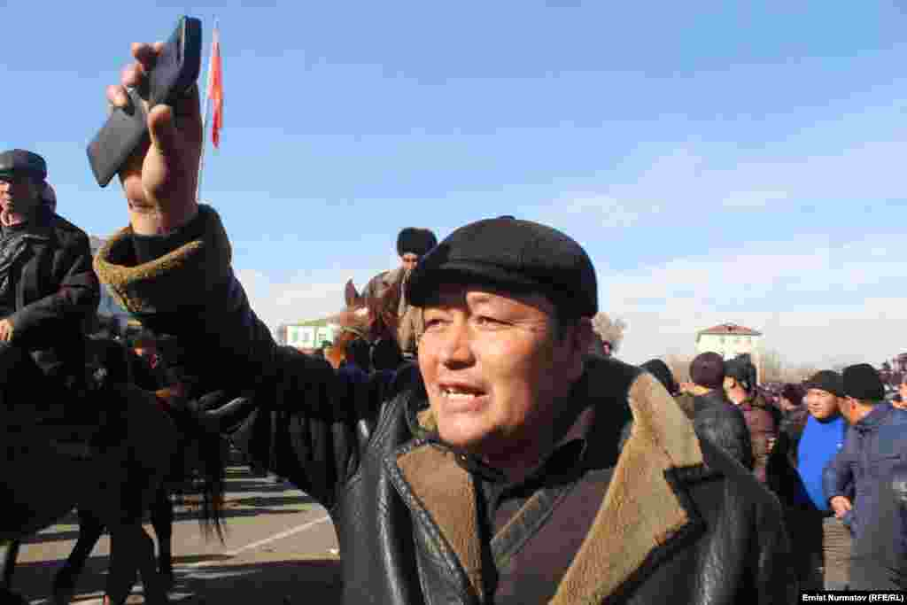 A numbers of protesters stood and chanted. Some threw stones, and at least one burned a portrait of Kyrgyzstan's president, Almazbek Atambaev.