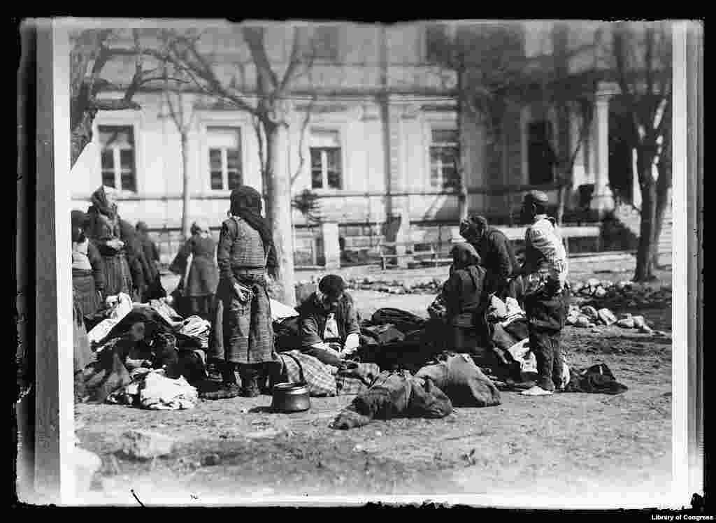 Refugees at an American Red Cross hospital in what is today North Macedonia in July 1919. The barefoot man on the right had just visited the bathhouse in the background. The others are waiting their turn. Bathing was compulsory to prevent the spread of typhus.