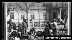 13. დევნილები ამერიკული წითელი ჯვრის საავადმყოფოში 1919 წლის ივლისში. დღეს ეს ადგილი უკვე ჩრდილოეთი მაკედონიაა. ფეხშიშველი მამაკაცი მარჯვნივ ახალი გამოსულია აბანოდან, რომელიც უკან, ფონზე მოჩანს. სხვები საკუთარ რიგს ელოდებიან. ჰიგიენის დაცვა სავალდებულო იყო ტიფის გავრცელების პრევენციისთვის.
