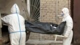 Барнаул ауруханасындағы мәйітхананың алдында тұрған медицина қызметкерлері. 22 қазан 2020 жыл. Ресей демографы Алексей Ракшаның пікірінше, денсаулық сақтау министрлігі коронавирустан көз жұмған көп науқасты басқа себептен өлді деп көрсеткен.