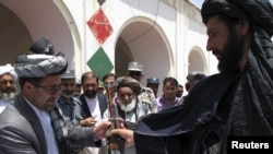 The governor of Afghanistan's southern Helmand Province receives a rifle from a Taliban fighter who said he wanted to return to normal life. Kabul hopes to make such moves more common.