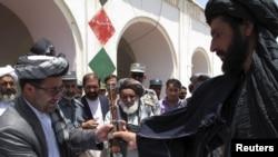 Гелманд провинциясынын губерантору Гүляб Мангал(солдо) урушту токтотууну каалаган талибан кыймылынын мүчөсүнүн автоматын ырасмий салтанатта өткөрүп алууда. 24-май 2011