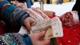 A meat vendor counts Russian rubles at an open-air food fair in Krasnoyarsk, Siberia.