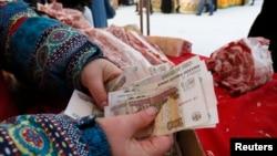 Продавачка брои рубли на пазар в Красноярс, Сибир.