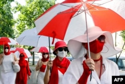 Belarusian women march down the street holding umbrellas in the colors of the former white-red-white flag of Belarus to show their solidarity with imprisoned protesters and opposition figures in Minsk on July 18.