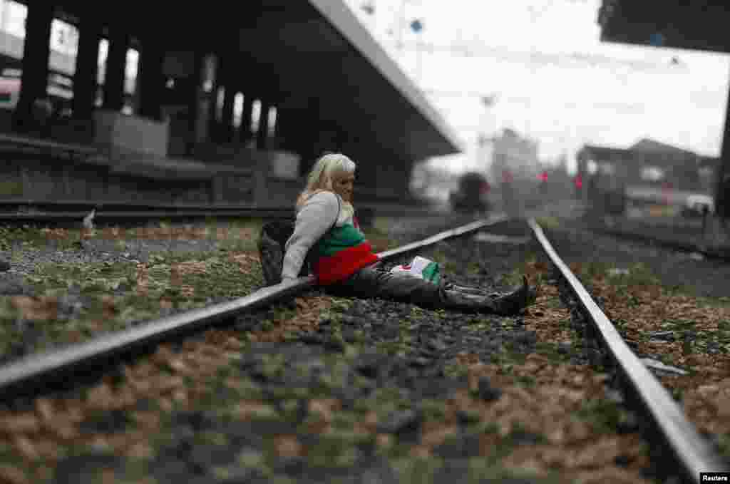 A protester, wearing a sweater in the colors of the Bulgarian national flag, sits on the tracks as demonstrators block the main railway station in Sofia. Hundreds of Bulgarians took to the streets in a dispute against monopolies and widespread corruption. (Reuters/Stoyan Nenov)