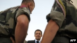 French President Nicolas Sarkozy (center) speaks with troops in Afghanistan on August 20 after 10 French soldiers were killed.