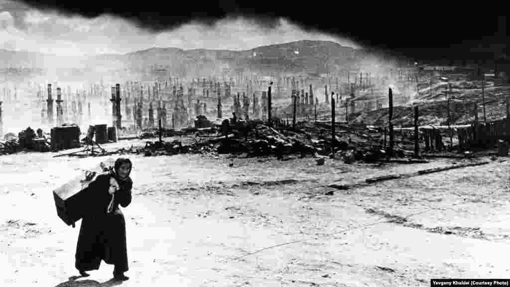 """Советский Мурманск после того, как нацистские войска в 1942 году уничтожили весь северо-запад города зажигательными бомбами: за сутки их было сброшено более 350 штук. Халдей вспоминал, что женщина ругала его за то, что он фотографировал разрушения. """"Почему вы вам не поехать в Берлин и снять, как наши пилоты бомбят их?"""" – говорила она. Фотограф пообещал ей, что, если когда-нибудь доберется до Германии, он """"именно это и сделает"""""""